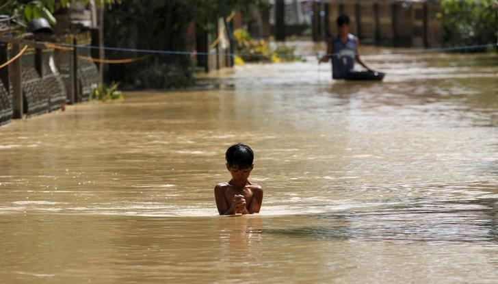 A boy wades through a flooded street in Jaen, Nueva Ecija in northern Philippines October 20, 2015, after the province was hit by Typhoon Koppu. REUTERS/Erik De Castro