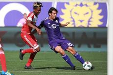 Apr 17, 2016; Orlando, FL, USA; Orlando City SC midfielder Kaka (10) kicks the ball as New England Revolution defender London Woodberry (28) defends during the second half at Orlando Citrus Bowl Stadium. Kim Klement-USA TODAY Sports