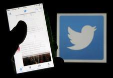 Человек читает сообщения в соцсети Twitter на фоне её логотипа в Бордо 10 марта 2016. Пользователи сервиса микроблогов Twitter Inc скоро получат больше свободы в написании твитов, поскольку компания планирует перестать учитывать фотографии и ссылки при подсчёте длины сообщений, которая ограничивается 140 знаками, сообщило агентство Bloomberg. REUTERS/Regis Duvignau/Illustration/File Photo