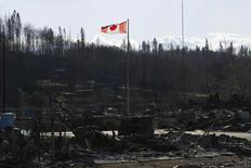A Canadian flag flies over damage caused by a wildfire, which prompted the mass evacuation of over 88,000 people, in Fort McMurray, Alberta, Canada on May 14, 2016. Chris Schwarz/Government of Alberta/Handout via REUTERS