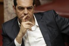 Алексис Ципрас на парламентской сессии в Афинах. Греческие законодатели одобрили повышение налогов и создание нового приватизационного фонда в воскресенье, а также либерализацию правил продажи банками невозвратных кредитов в обмен на столь необходимые займы и списание долга. REUTERS/Michalis Karagiannis