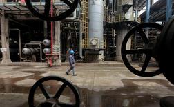 Рабочий на НПЗ в китайском городе Ухань в провинции Хубэй, 23 марта 2012 года. Цены на нефть упали на слабых торгах во вторник на фоне укрепления доллара, однако потери были ограничены вероятным снижением запасов нефти и бензина в США. REUTERS/Stringer/File Photo