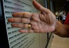 Un oficial de seguridad tapa un tablero que muestra el banco suizo BSI, en sus oficinas en Singapur. 24 de mayo de 2016. El banco central de Singapur ordenó el martes el cierre de las operaciones de BSI en la ciudad estado, luego de que Suiza abrió un proceso penal contra el banco privado basado en su investigación sobre las transacciones del fondo estatal de Malasia, 1MDB. REUTERS/Edgar Su