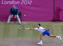 Serbia's Novak Djokovic reaches for a return to Argentina's Juan Martin del Potro in the men's singles tennis bronze medal match at the All England Lawn Tennis Club during the London 2012 Olympic Games August 5, 2012.     REUTERS/Adrees Latif