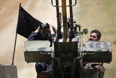 """Боевики исламистской группировки """"Фронт ан-Нусра"""" у линии фронта в районе провинции Идлиб ведут наблюдение в ожидании авиаударов сил сирийского президента Башара Асада 17 мая 2014 года. Российское Минобороны объявило в среду о временном прекращении ударов по позициям радикального """"Фронта ан-Нусра"""" в Сирии до тех пор, пока от них не отделятся вооруженные формирования, готовые к прекращению боевых действий. REUTERS/Hamid Khatib"""