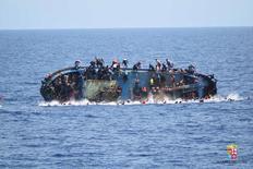 Imigrantes são vistos em barco virado antes da chegada do resgate na costa da Líbia, em foto distribuída pela Marinha da Itália. 25/05/2016 Marina Militare/Handout via REUTERS