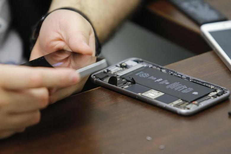 A worker checks an iPhone in a repair store in New York, February 17, 2016. REUTERS/Eduardo Munoz