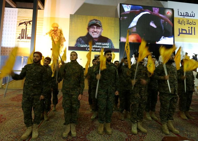 Members of Lebanon's Hezbollah wave flags after Hezbollah leader Sayyed Hassan Nasrallah addressed them from a screen in Beirut's southern suburbs, Lebanon May 20, 2016. REUTERS/Aziz Taher