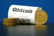 Santander se convertirá en el primer banco entre los que opera en Reino Unido en emplear para el registro de pagos internacionales la tecnología que está detrás de la moneda virtual Bitcoin y podría empezar a desplegar el servicio a sus clientes el año que viene, dijo esta semana el responsable de innovación de Santander UK.  En la imagen de archivo, monedas representando a la divisa virtual Bitcoin junto a un ticket con un código QR, el 27 de mayo de 2015.  REUTERS/Benoit Tessier