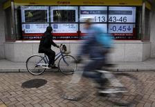 Un hombre en bicicleta mira un tablero electrónico, afuera de una correduría en Tokio, Japón. 29 de febrero de 2016. Las bolsas de Asia bajaban el lunes y el dólar repuntaba después de que la presidenta de la Reserva Federal de Estados Unidos, Janet Yellen, sugirió que una subida de las tasas de interés en su país podría estar cerca. REUTERS/Yuya Shino
