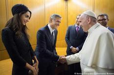 En la imagen, el Papa Francisco se reúne con el actor estadounidense George Clooney (C) y su mujer Amal (I) durante un encuentro de Scholas Occurrentes en el Vaticano, el 29 de mayo de 2016. El Papa Francisco entregó el domingo medallas a los actores estadounidenses Richard Gere y George Clooney y a la actriz mexicana Salma Hayek en un evento celebrado en el Vaticano para promocionar el trabajo de Scholas Occurrentes, una organización promovida por el pontífice. Osservatore Romano/ Handout