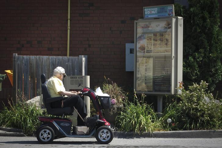 A man on a wheel scooter places an order at a Tim Hortons drive-thru restaurant in Bobcaygeon, Ontario August 9, 2014.        REUTERS/Carlo Allegri