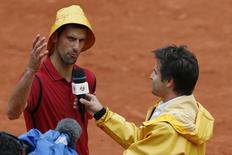Tennis - French Open - Roland Garros - Novak Djokovic of Serbia v Roberto Bautista Agut of Spain - Paris, France - 1/06/16. Novak Djokovic wears a rain hat as he answers to former French tennis player Arnaud Clement. REUTERS/Pascal Rossignol