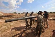 """Боевики Первого полка, входящего в Свободную сирийскую армию, готовятся запустить ракету из Града в пригороде Алеппо. 29 мая 2016 года. Тысячи поддерживаемых США бойцов начали новое мощное наступление в Сирии, пытаясь оттеснить """"Исламское государство"""" из районов на севере страны, которые боевики используют в качестве базы снабжения. REUTERS/Abdalrhman Ismail"""