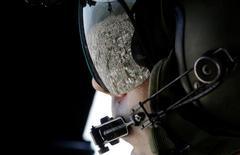 Favela refletida em óculos de militar durante sobrevoo realizado como parte de exercício de segurança para os Jogos Rio 2016. 06/04/2016 REUTERS/Ricardo Moraes