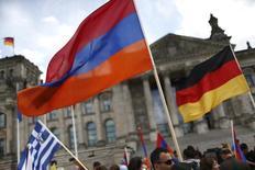 Люди держат армянские и немецкие флаги, стоя перед Рейхстагом. Бундестаг Германии в четверг проголосовал в пользу символичной резолюции о признании массовых убийств армян в Османской империи в 1915 году геноцидом. REUTERS/Hannibal Hanschke