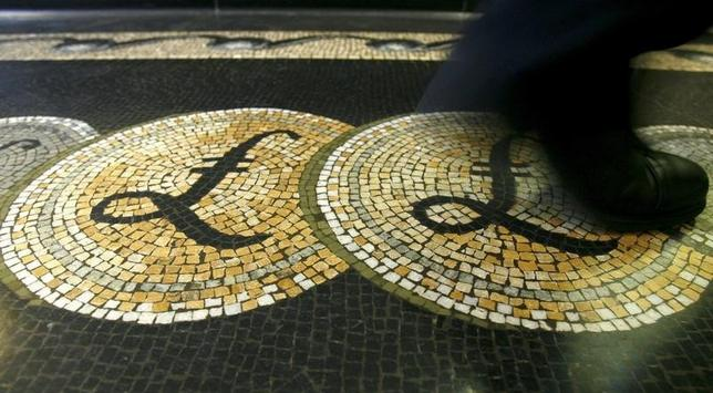 An employee is seen walking over a mosaic of pound sterling symbols set in the floor of the front hall of the Bank of England in London, in this March 25, 2008 file photograph.   REUTERS/Luke MacGregor/Files