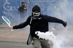 Manifestante rebatendo lata de gás com raquete de tênis durante protesto contra reforma das leis trabalhistas na França.    02/06/2016     REUTERS/Stephane Mahe