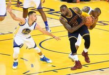 June 2, 2016; Oakland, CA, USA; Cleveland Cavaliers forward LeBron James (23) controls the ball against Golden State Warriors  Stephen Curry (30) and forward Andre Iguodala (9) during the first half in game one of the NBA Finals at Oracle Arena. Mandatory Credit: Bob Donnan-USA TODAY Sports