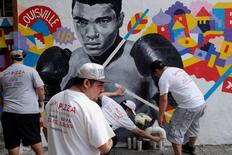 Employees of Joe's Pizza build a makeshift memorial to the late Muhammad Ali near a mural in New York. REUTERS/Lucas Jackson