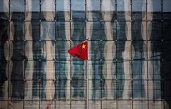 Una bandera de China ondea en la sede de un banco comercial en una calle financiera, cerca del Banco Central chino, en Pekín. 24 de noviembre de 2014. China permitirá que las compañías extranjeras de tarjetas de crédito operen en el país, ofreciendo potencialmente a grupos como Visa Inc y MasterCard acceso a un mercado de 55 billones de yuanes (8,4 billones de dólares) de pagos a través de tarjetas bancarias. REUTERS/Kim Kyung-Hoon/File Photo