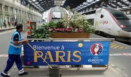 Trabalhador passa por faixa que dá as boas-vindas à Euro 2016 em estação de trem em Paris. 07/06/2016 REUTERS/Charles Platiau
