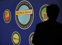 La silueta de un hombre se ve frente al logo del Banco Mundial en la entrada a la reunión anual del Fondo Monetario Internacional (FMI) y del BM en Tokio, 10 de octubre de 2012.  El Banco Mundial recortó el miércoles su estimación de crecimiento global a un 2,4 por ciento desde el 2,9 por ciento que proyectó en enero, debido a los bajos precios de las materias primas, una tibia demanda en las economías avanzadas, la debilidad del comercio y menores flujos de capital. REUTERS/Kim Kyung-Hoon