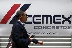 Un hombre camina delante del logo de la compañía mexicana Cemex, en la Avenida de la Reforma, en Ciudad de México, México. 27 de agosto de 2014. La cementera mexicana Cemex está ofreciendo un bono a 8 años, no redimible hasta el cuarto año, por 400 millones de euros, informó el miércoles IFR, un servicio de información financiera de Thomson Reuters. REUTERS/Edgard Garrido