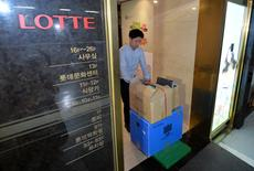 An investigator from the prosecution office carries boxes containing confiscated articles at Lotte Group's headquarters in Seoul, South Korea, June 10, 2016.   Choi Jae-gu/Yonhap via REUTERS