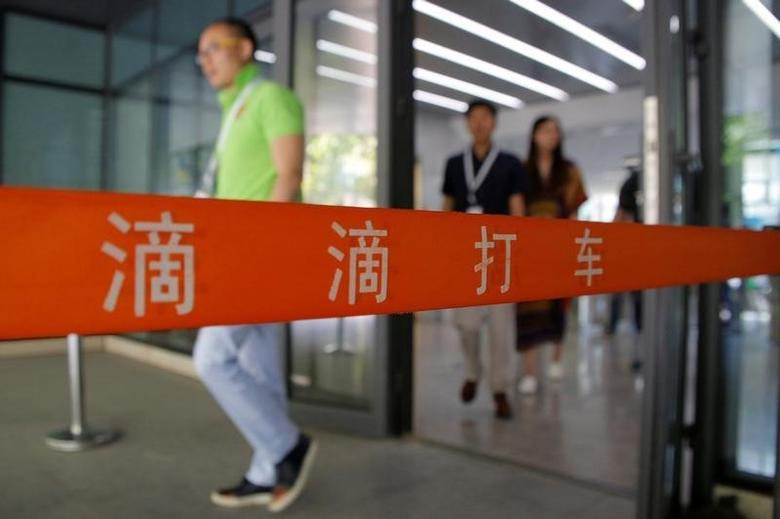 People walk out of the headquarters building of Didi Chuxing in Beijing, China, May 18, 2016. REUTERS/Kim Kyung-Hoon