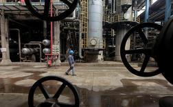 Un trabajador camina entre tuberías de las refinería de Wuhan en la provincia china de Hubei. 23 de marzo de 2012. El crecimiento de la inversión en activos fijos en China bajó a un 9,6 por ciento en enero a mayo, respecto del mismo período del año anterior, lo que fue menor a las expectativas del mercado. REUTERS/Colaborador/Archivo