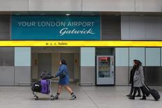 Travelers pass a sign for Gatwick Airport in southern Britain, December 17, 2015. CalPERS, the biggest U.S. public pension fund, made its first direct infrastructure investment in 2010, when it purchased a stake of London's Gatwick Airport.   REUTERS/Neil Hall/File Photo