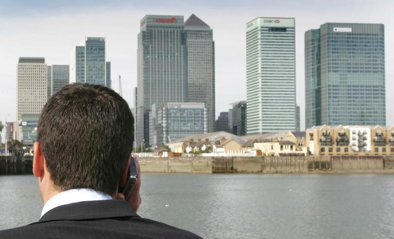 A man speaks on his mobile phone while standing on a boat on the River Thames with Canary Wharf and the financial district of London seen in the background. REUTERS/Toby Melville