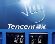 Dancers perform underneath the logo of Tencent at the Global Mobile Internet Conference in Beijing May 6, 2014. REUTERS/Kim Kyung-Hoon/File Photo