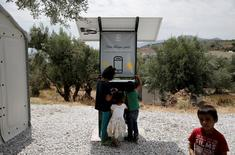 Children stand around a solar powered charging station for mobile devices designed by a group of university students, at the municipality-run camp of Kara Tepe on the island of Lesbos, Greece, June 14, 2016. REUTERS/Alkis Konstantinidis