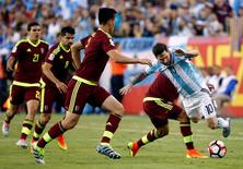 Argentina midfielder Lionel Messi (10) is tripped while being surrounded by Venezuelan players during the second half of Argentina's 4-1 win over Venezuela in quarter-final play in the 2016 Copa America Centenario soccer tournament at Gillette Stadium. Mandatory Credit: Winslow Townson-USA TODAY Sports