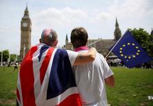 La divergencia entre los mercados de bonos de la zona euro, acentuada por las preocupaciones sobre el inminente referéndum de Reino Unido sobre su pertenencia a la UE, se reducía el lunes por segundo día consecutivo después de que las encuestas dieran algo de impulso al campo favorable a la permanencia.  En la imagen, dos personas que participaron en un evento pro-UE con una bandera británica y una de la UE, cerca del Big Ben, en Parliament Square, Londres, 19 de junio de 2016. REUTERS/Neil Hall