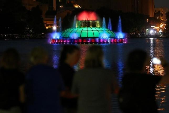 People take part in a vigil for the Pulse night club victims as the Lake Enola fountain is lit in rainbow colors following last week's shooting in Orlando, Florida, U.S., June 19, 2016.  REUTERS/Carlo Allegri