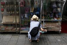 A shopper looks at items outside a discount store at a shopping district in Tokyo, June 18, 2015.   REUTERS/Yuya Shino/File Photo