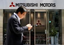 Прохожий идет мимо штаб-квартиры Mitsubishi Motors Corp в Токио. Mitsubishi Motors Corp обнародовала прогноз чистого убытка в 145 миллиардов иен ($1,4 миллиарда) на текущий финансовый год из-за крупных затрат на компенсации и падения продаж на фоне скандала с подтасовкой данных о расходе топлива. REUTERS/Issei Kato/File Photo