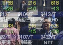 Personas se reflejan en una pantalla electrónica que muestra índices bursátiles, afuera de una correduría en Tokio, Japón.  18 de abril de 2016. Las bolsas de Asia subían el miércoles en medio de las expectativas de que el Reino Unido vote por seguir en la Unión Europea, y luego de que el testimonio de la presidenta de la Reserva Federal de Estados Unidos, Janet Yellen, prácticamente llevó a descartar una subida de las tasas de interés en julio. REUTERS/Toru Hanai