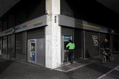En la imagen de archivo, una mujer usa un cajero automático en una sucursal de un banco en Atenas. El Banco Central Europeo restableció el miércoles el acceso de los bancos de Grecia a las operaciones de financiamiento barato, lo que permite a los prestamistas salir de una costosa línea de emergencia tras más de un año y dijo que examinará más adelante si agrega la deuda griega a su programa de compra de activos. REUTERS/Michalis Karagiannis