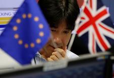Reino Unido votó por abandonar la Unión Europea, mostraron los resultados del referéndum del jueves, un resultado que deja al país en un sendero de incertidumbre y que asesta el mayor golpe a los esfuerzos de unión del continente desde la Segunda Guerra Mundial.  En la imagen, un empleado de una empresa de trading entre una bandera europea y de Reino Unido en Tokio, el 24 de junio de 2016. REUTERS/Issei Kato