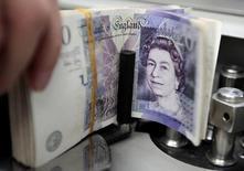 Банковский служащий подсчитывает британские фунты в банке Бангкока. Фунт стерлингов переживает самую волатильную сессию в современной истории и достиг минимума с 1985 года, поскольку британцы проголосовали за выход из ЕС, спровоцировав бегство в безопасные валюты, такие как иена и доллар.  REUTERS/Sukree Sukplang/File Photo