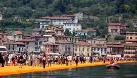 People walk on the installation 'The Floating Piers' by Bulgarian-born artist Christo Vladimirov Yavachev, known as Christo, on the Lake Iseo, northern Italy, June 24, 2016. REUTERS/Stefano Rellandini