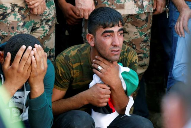 Brothers of Belal Al-Zuhbe, one of the solders killed in an attack on a border military post near a camp for Syrian refugees, cry during Al-Zuhbe's funeral at Nahleh village in the city of Jerash, north of Amman, Jordan, June 21, 2016. REUTERS/Muhammad Hamed