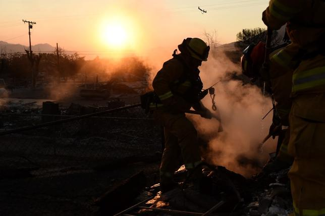 Firefighter Robert Aikman extinguishes a hot spot at a residence leveled by the Erskine Fire in South Lake, California, U.S. June 26, 2016. REUTERS/Noah Berger