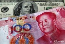 Банкноты в 100 юаней и 100 долларов. Государственные банки Китая, возможно, начали продавать доллары от имени центробанка для поддержки юаня в четверг, после того как Рейтер сообщил о том, что Пекин хочет дать национальной валюте опуститься до 6,80 за доллар в этом году, сказали трейдеры.  REUTERS/Nicky Loh