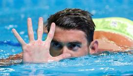 Michael Phelps holds up five fingers during the finals for the men's 200 meter butterfly in the U.S. Olympic swimming team trialsin Omaha, Nebraska.  Erich Schlegel-USA TODAY Sports