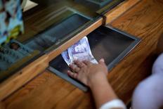 Una mujer cambia billetes de libras esterlinas por euros, en una casa de cambio en Gibraltar. 24 de junio de 2016. El déficit en cuenta corriente de Reino Unido no se redujo como era previsto en los primeros tres meses de este año y se mantuvo cerca de un máximo histórico, mostraron el jueves datos oficiales. REUTERS/Jon Nazca